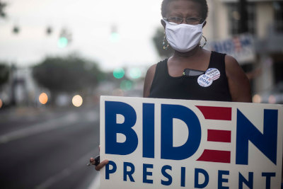 woman wearing white mask with biden for president sign