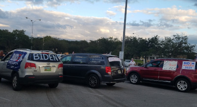 cars with signs for biden caravan