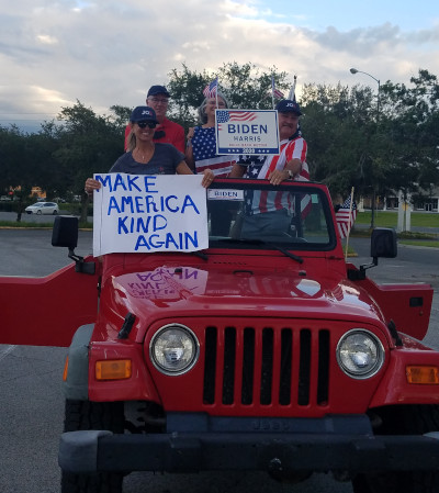 four people standing in red truck with biden signs