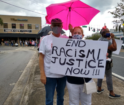 couple with end racism justice now sign