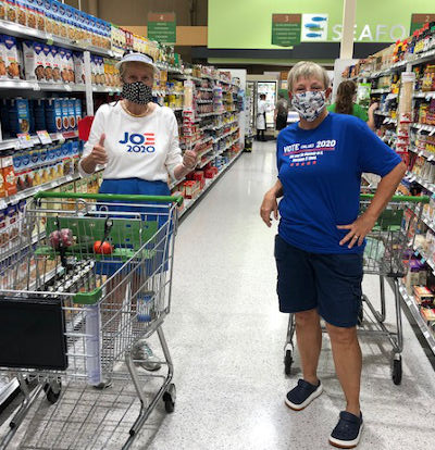 two women in grocery wearing democrat t-shirts and masks