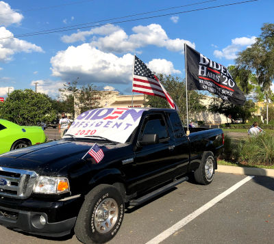 black pickup truck with biden sign and flags