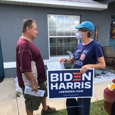 woman with biden-harris sign talking to man