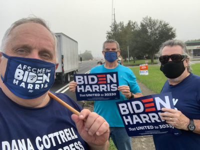 three men with masks and biden signs