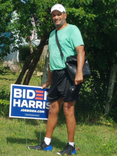 man outside with biden harris sign