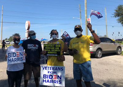four sign wavers posing at event