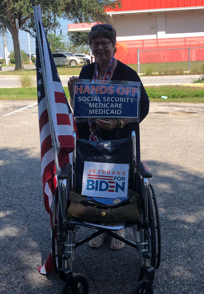 veterans for biden woman standing with flag and wheelchari