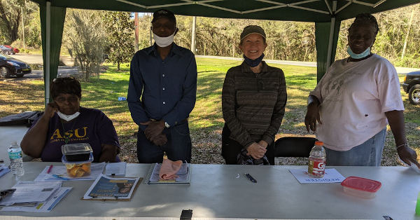 four people at voter registration table